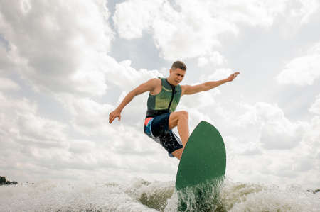 Photo pour caucasian male rides the waves in a summer river,having healthy extreme summertime,on the background of the sky - image libre de droit
