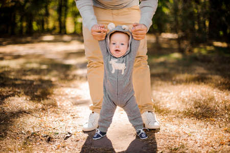 Photo for Man walking with a cute smiling baby boy in beautiful park on the bright day - Royalty Free Image