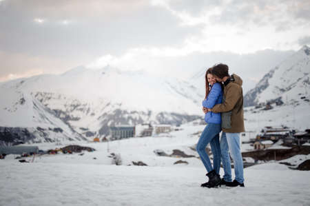 tender young couple of lovers, in jeans and warm jackets, hugging each other against the background of snow mountains and laughing
