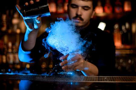 Foto de Male bartender uses metal shaker to mix an alcohol drink - Imagen libre de derechos