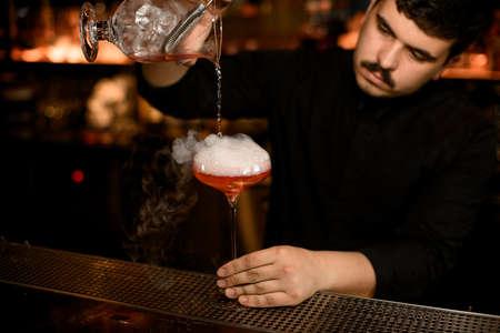 Foto de Bartender uses strainer to pour an alcohol drink - Imagen libre de derechos