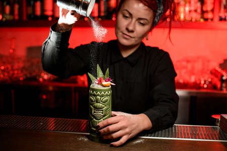 Foto per Cute bartender girl serving alcoholic cocktail in the Tiki mug sprinkling on it with sugar powder - Immagine Royalty Free