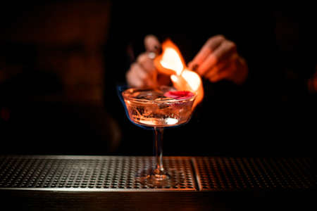 Foto per Woman bartender serving on fire alcoholic transparent cocktail with ice in the glass decorated with a pink rose bud - Immagine Royalty Free