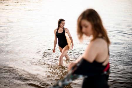 Foto de young woman in swimsuit comes out of the water - Imagen libre de derechos
