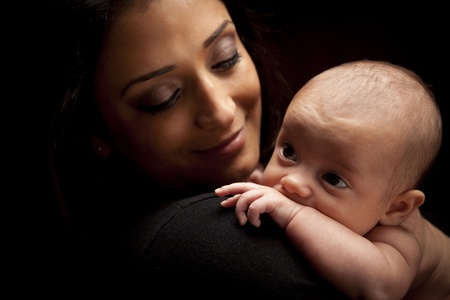 Photo for Young Attractive Ethnic Woman Holding Her Newborn Baby Under Dramatic Lighting. - Royalty Free Image