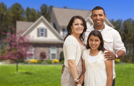 Photo pour Happy Hispanic Mother, Father and Daughter in Front of Their Home. - image libre de droit