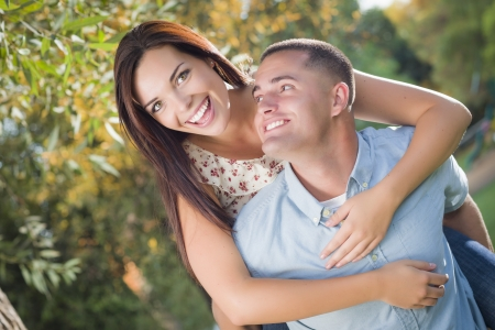Photo for Happy Mixed Race Romantic Couple Piggyback Portrait in the Park. - Royalty Free Image