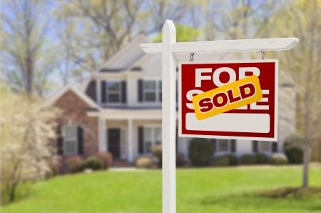 Foto de Sold Home For Sale Real Estate Sign in Front of Beautiful New House. - Imagen libre de derechos
