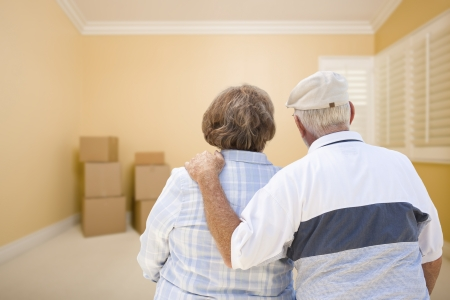 Photo for Hugging Senior Couple In Room Looking at Moving Boxes on the Floor. - Royalty Free Image