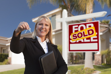 Photo pour Female Real Estate Agent Handing Over the House Keys in Front of a Beautiful New Home and Real Estate Sign. - image libre de droit