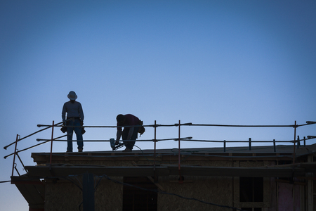 Photo pour Construction Workers Silhouette on Roof of Building  - image libre de droit