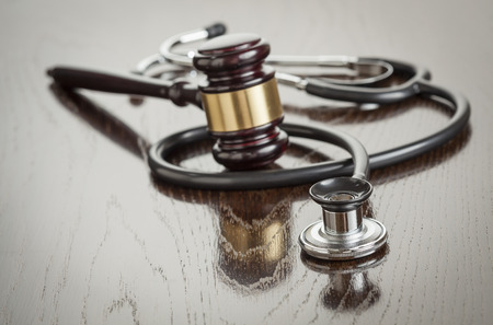 Photo for Gavel and Stethoscope on Reflective Wooden Table. - Royalty Free Image