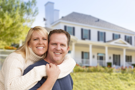 Photo for Happy Couple Hugging in Front of Beautiful House. - Royalty Free Image