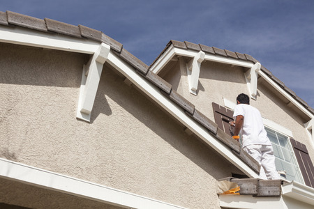 Photo for Busy House Painter Painting the Trim And Shutters of A Home. - Royalty Free Image