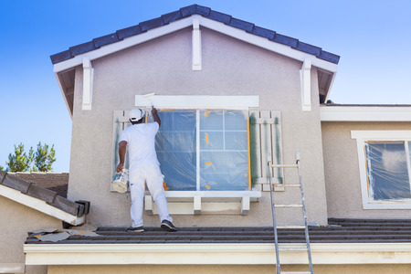 Photo pour Busy House Painter Painting the Trim And Shutters of A Home. - image libre de droit