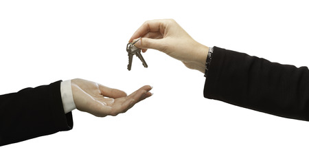 Foto de Woman Handing Over Woman Set Of New Keys Isolated on White. - Imagen libre de derechos