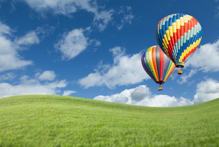 Photo for Two Hot Air Balloons Up In The Beautiful Blue Sky With Grass Field Below. - Royalty Free Image