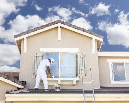 Photo pour Busy House Painter Painting the Trim And Shutters of A Home. - image libre de droit