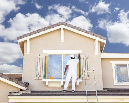 Foto de Busy House Painter Painting the Trim And Shutters of A Home. - Imagen libre de derechos