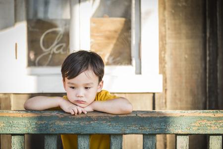Foto de Melancholy Mixed Race Boy Leaning on Porch Railing. - Imagen libre de derechos