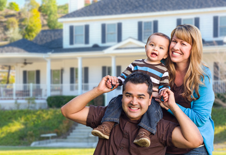 Photo pour Happy Mixed Race Young Family in Front Yard of Beautiful House. - image libre de droit