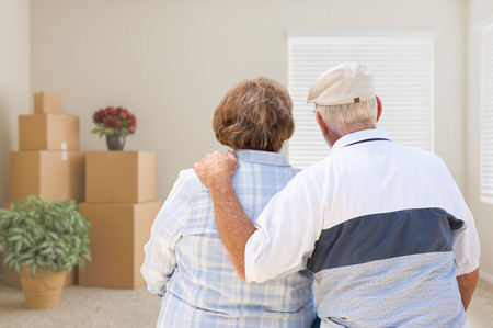Photo pour Senior Couple Facing Empty Room with Packed Moving Boxes and Potted Plants. - image libre de droit