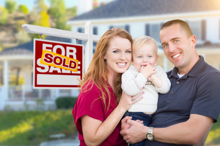 Foto de Happy Young Military Family in Front of Sold For Sale Real Estate Sign and New House. - Imagen libre de derechos