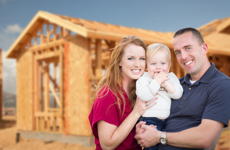 Photo for Happy Young Military Family Outside Their New Home Framing at the Construction Site. - Royalty Free Image
