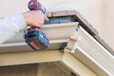 Photo pour Worker Attaching Aluminum Rain Gutter to Fascia of House. - image libre de droit