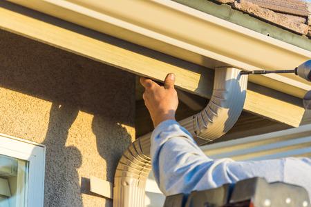 Photo pour Worker Attaching Aluminum Rain Gutter and Down Spout to Fascia of House. - image libre de droit