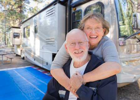 Photo for Senior Couple In Front of Their Beautiful RV At The Campground. - Royalty Free Image