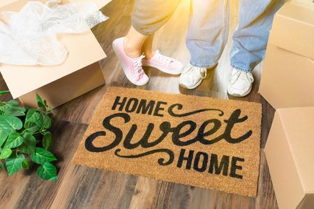 Foto de Man and Woman Standing Near Home Sweet Home Welcome Mat, Moving Boxes and Plant. - Imagen libre de derechos
