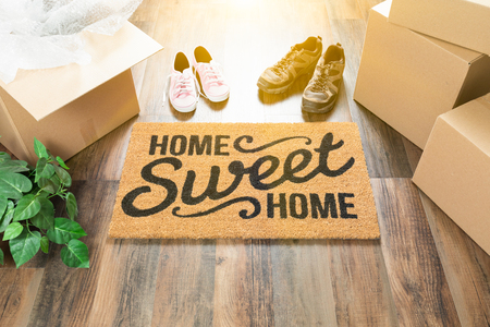 Photo for Home Sweet Home Welcome Mat, Moving Boxes, Women and Male Shoes and Plant on Hard Wood Floors. - Royalty Free Image