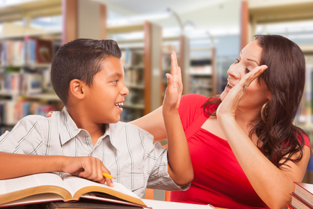 Foto de Hispanic Young Boy and Famle Adult High Five Whilte Studying At Library. - Imagen libre de derechos