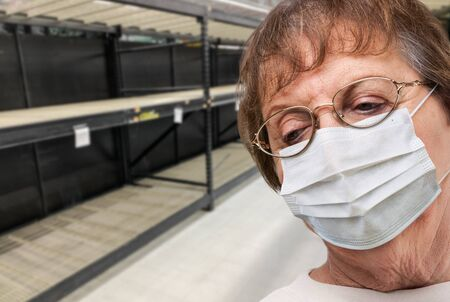 Photo for Senior Adult Woman In Medical Face Mask Walking Down Empty Aisle of Grocery Store. - Royalty Free Image