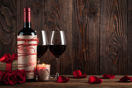 Foto de Red wine bottle, two glasses of wine, gift box, candle and red roses on the dark wooden background - Imagen libre de derechos