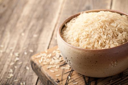 Foto de Uncooked parboiled rice in a bowl on wooden table - Imagen libre de derechos