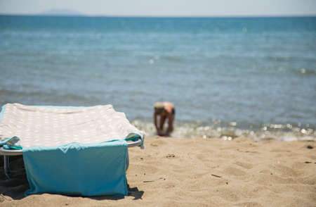 Foto de image of sun lounger on the beach with sea and child in the background - Imagen libre de derechos