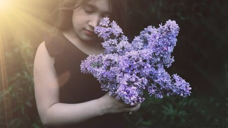 Photo for Cute little girl smelling lilac. Person holding flowers on dark natural background. Child enjoying bouquet outside. Going to park, forest in summer and spring. Connection with nature idea - Royalty Free Image
