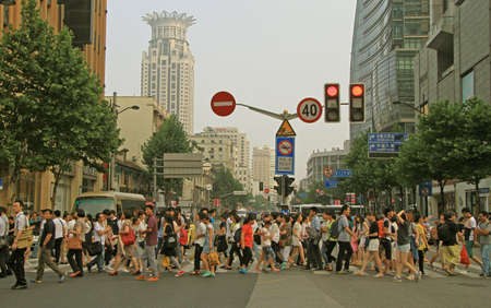 Photo pour Shanghai, China - July 1, 2015: people are crossing road by crosswalk in Shanghai, China - image libre de droit