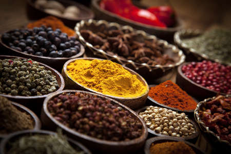 Photo for A selection of various colorful spices on a wooden table in bowls - Royalty Free Image