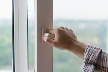 Foto de Male hand opens a window - Imagen libre de derechos