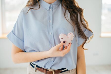Photo pour Picture of a small white heart in hands, female holds handmade sewn soft toy,  woman with Valentine gift, happy girl smiling, conceptual image of health care or love - image libre de droit