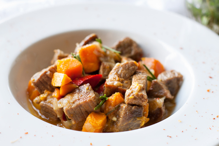 Foto de Beef stew with butternut squash, pepper and onion decorated with fresh rosemary in white plate on marble table - Imagen libre de derechos
