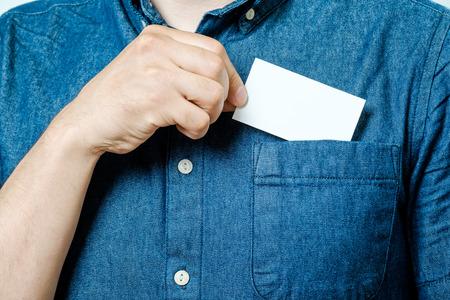 Foto de Man's hand takes out blank business card from the pocket of blue shirt - Imagen libre de derechos