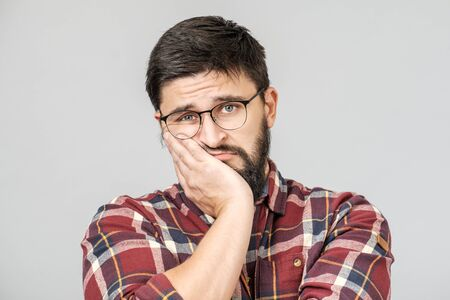 Foto de Portrait of unhappy determined european male thinking and looking with serious and worried look, standing against gray background - Imagen libre de derechos