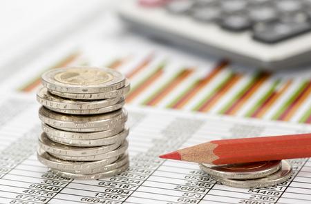 Foto de stacked euro coins on table sheet with chart of exchange market - Imagen libre de derechos