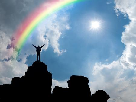 Foto de Happy man standing at mountain top, sun and rainbow in blue sky - Imagen libre de derechos