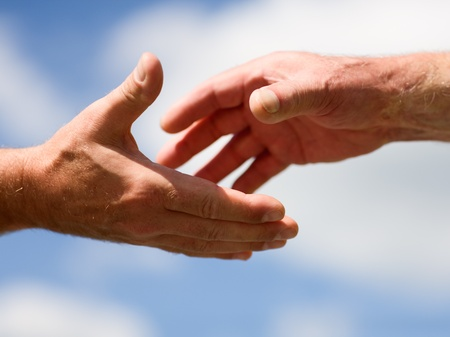 Photo for Two hands reaching out to each other against blue sky - Royalty Free Image