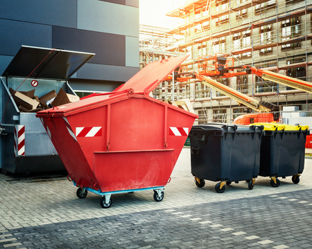 Foto de Red dumpster, recycle, waste and garbage bins near new office building. Construction site on background - Imagen libre de derechos